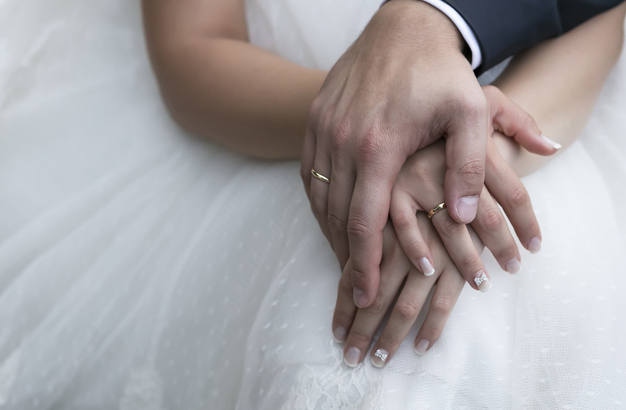 Bride and groom's hands with wedding rings (soft focus) .Cross p